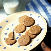Ginger biscuits on plate with blue stars; glass of milk