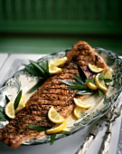 Barbecued salmon with lemons and bay leaves on platter