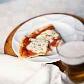 Zwei kleine Stückchen Pizza auf Teller, davor Glas mit Bier