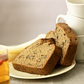 Two slices of banana and walnut bread beside coffee cups