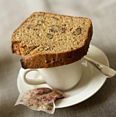 A slice of banana and walnut bread on tea cup