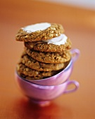 A Stack of Frosted Oatmeal Cookies on Two Purple Tea Cups