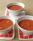 Tomato soup in three white bowls