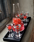 Raspberry cocktails in glasses and decanter on a rectangular tray by a window