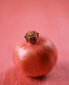 A Single Pomegranate on a Pink Background