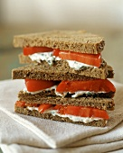 Triple Layer Sandwich with Herbed Cheese and Tomatoes on Whole Wheat Bread