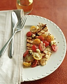 A Grilled Boneless Chicken Breast with Red and Yellow Cherry Tomatoes and Feta Cheese