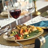 Chicken with stuffing and vegetables, glass of red wine
