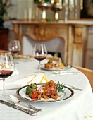 Laid table with poultry dish and red wine