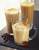 Three Cold Coffee Drinks with Cream: One with Cinnamon and Anise, Two Frappes with Straws