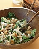 Caesar salad with grilled chicken in wooden bowl