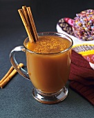 Hot apple punch with cinnamon sticks in glass