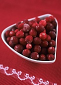Cranberries in white bowl on red tablecloth