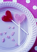 Heart-shaped lollies on blue plastic plate