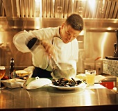 A Chef Preparing Mussels in a Restaurant Kitchen