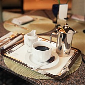 A Cup of Black Coffe on a Tray with Small Pot and Creamer