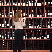 A Woman Examining a Wine Bottle in a Wine Store
