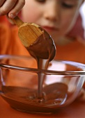 Small girl stirring chocolate cream with wooden spoon
