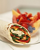 Wrap with vegetable filling, fruit salad behind