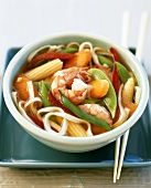 Asian noodle soup with shrimps and vegetables in small bowl