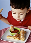 Boy dipping strips of pizza bread into bowl of tomato sauce