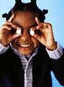 Mädchen hält sich Zuckerwürfel vor die Augen