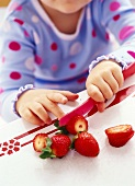Girl cutting strawberry with plastic knife
