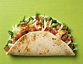 Taco shell with chicken, tomatoes, cheese and lettuce