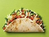 Taco-Shell mit Hähnchen, Tomaten, Käse und Salat