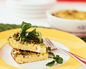 Two Slices of a Persian Omelet Stacked and Topped with Greens on a Plate