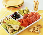 Antipasto in a Divided Dish; Serving Plates and Bread Sticks
