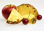 Pineapple wedges, red apple and cherries
