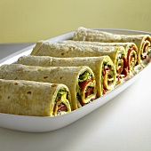 Six wraps filled with hummus and vegetables