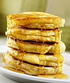 Maple syrup trickling over a pile of pancakes