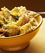 Pasta with vegetables and pine nuts in yellow bowl