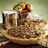 Whole apple & pecan pie; baking ingredients in background