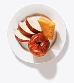 Roter Apfel, Apfelschnitze und Stück Cheddar auf Teller