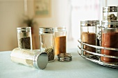 Spices in Glass Jars on a Table and in a Spice Rack
