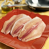 Fresh tilapia fillets on red plate