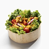 Mixed green salad with vegetables & croutons in wooden bowl