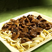 Beef ragout with mushrooms on ribbon pasta