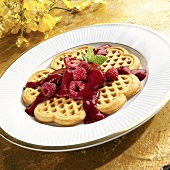 Heart-shaped waffles with berries and fruit sauce