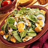 Spinach salad with chicken, egg, croutons and pesto