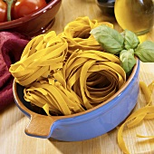 Saffron ribbon pasta in blue pan; tomatoes; olive oil