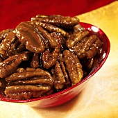 Caramelised pecan nuts in a red bowl