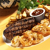 Barbecued steak and shrimps with dip and fried potatoes
