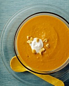 A Bowl of Creamy Carrot Soup with Peanuts and Sour Cream Garnish