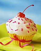 An Ice Cream Frosted Cupcake with Pink Sprinkles and a Cherry, Tied with a Ribbon