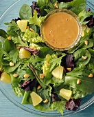A Mixed Green Salad with Pineapple, Nuts and Salad Dressing