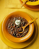 A Bowl of Black Bean Soup with Sour Cream and Cilantro and a Wooden Spoon
